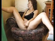 A brunette spreads her legs while she is handling herself